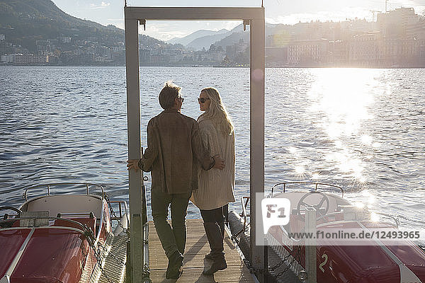Couple look off from end of lake pier