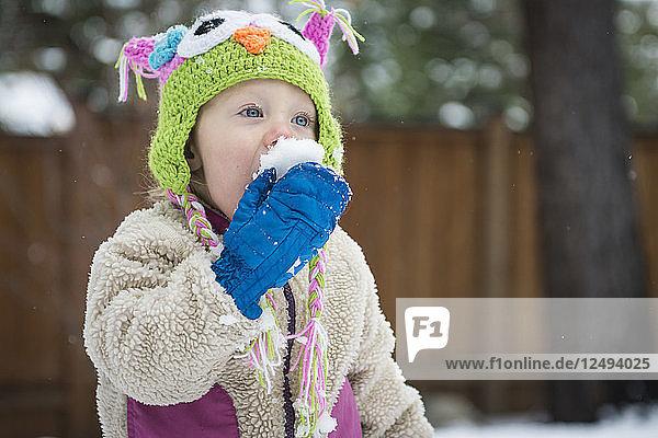 Toddler girl eats snowball  Lake Tahoe  California.