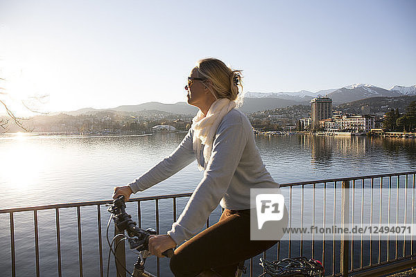 Woman rides bike on walkway with lake and city behind