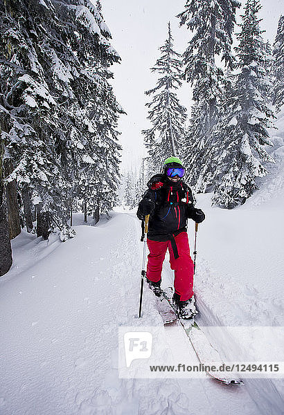A girl smiles as spitlboarding through pine trees on a snowy day in the backcountry.