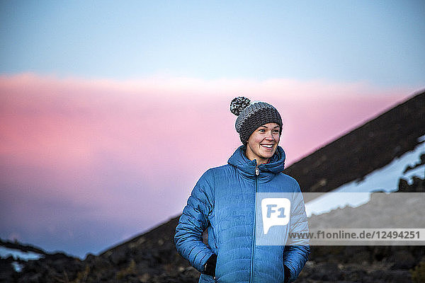 A woman in teal parka coat and wool hat stands in a sunset mountain scene.