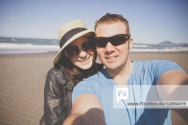 A couple take a selfie while on vacation along the Oregon Coast.