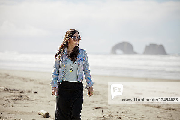 A fashionable woman walks along Rockaway Beach  Oregon.