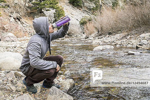 Young man drinking from water bottle near river