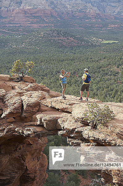Hikers on the Devil's Bridge in Red Rock-Secret Mountain Wilderness Area outside Sedona  Arizona May 2011. The Devil's Bridge is an easy two-mile hike with spectacular views.