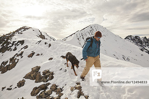 A hiker and his dog descend from the summit of Frosty Peak in Manning Provincial Park  British Columbia  Canada.