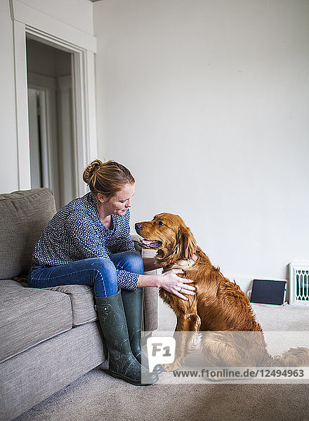 A young dog owner enjoys time with her dog in their home.