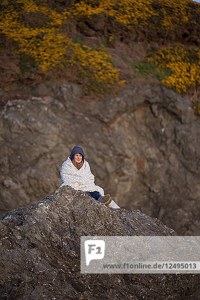 A young woman wrapped in a blanket sists on a rock bluff at Bandon Bay  Oregon.