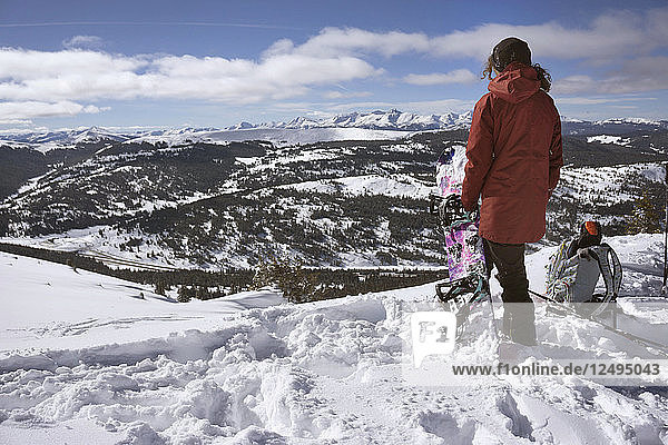 Snowboarder Sandra Hillen Looks Out Over The Rockies After Hiking Up On A Splitboard
