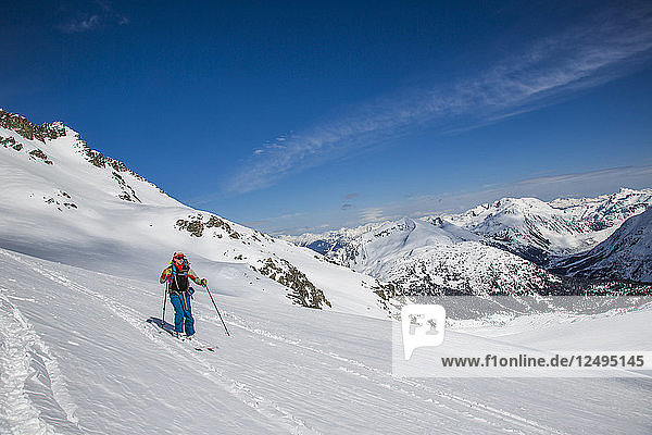 A skier descends to a notch during the Spearhead Traverse in the Coast Mountains of British Columbia  Canada.
