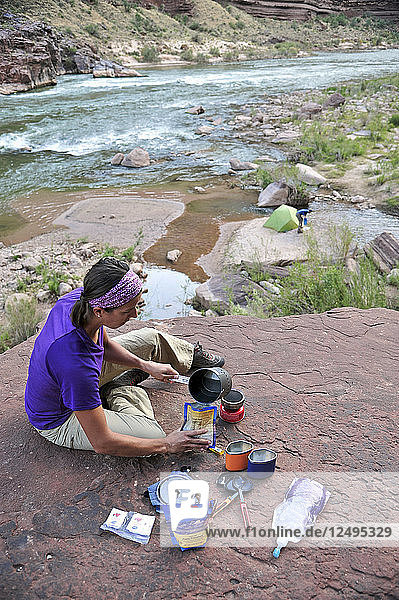 Female hiker cooks dinner on a cliff-pinched patio above camp and the Colorado River near Deer Creek Falls in the Grand Canyon outside of Fredonia  Arizona November 2011. The 21.4-mile loop starts at the Bill Hall trailhead on the North Rim and descends 2000-feet in 2.5-miles through Coconino Sandstone to the level Esplanada then descends further into the lower canyon through a break in the 400-foot-tall Redwall to access Surprise Valley. Hikers connect Thunder River and Tapeats Creek to a route along the Colorado River and climb out Deer Creek.