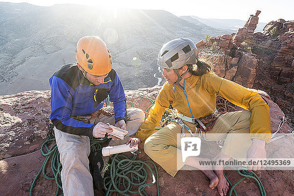 A man and woman reading the summit register after rock climbing a route called Psycho Path on Psycho Tower above the Big Gypsum Valley  Naturita  Colorado.