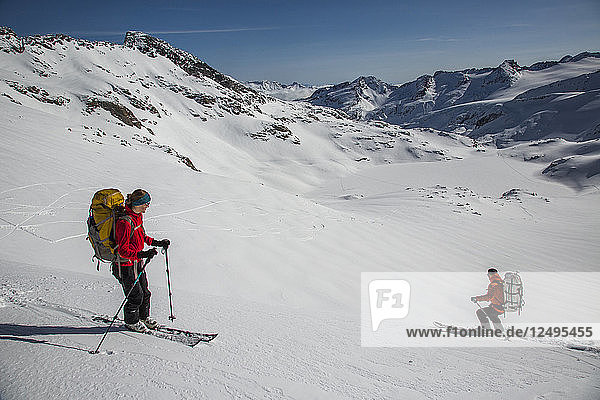 Skiers on a sunny day in the wide open terrain of the Spearhead Traverse out of Whistler  British Columbia  Canada.