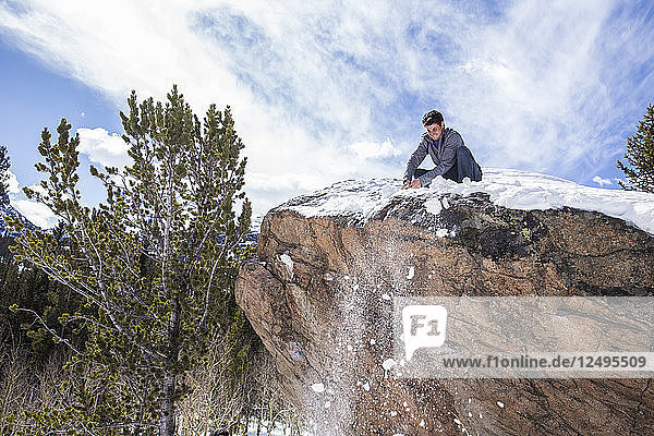 Male climber cleans snow from atop a boulder in Rocky Mountain National Park  Colorado