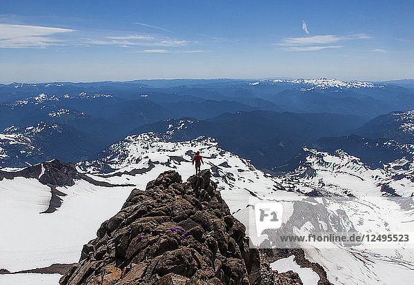 Long Exposure Of Man Standing On Top Of Rocky Mountain