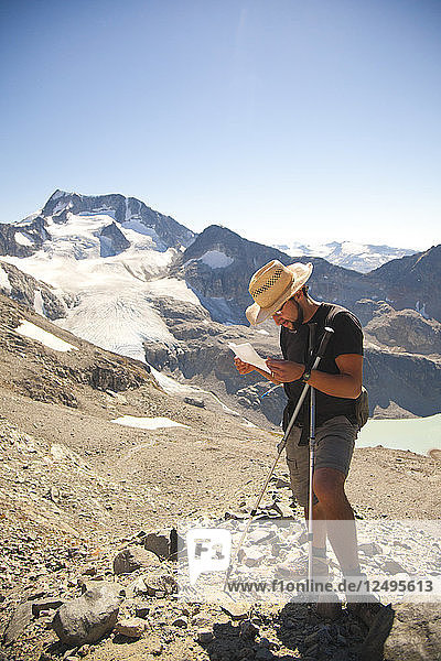 A hiker stops to read directions high in the mountains above Wedgemount Lake in Garibaldi Provincial Park.