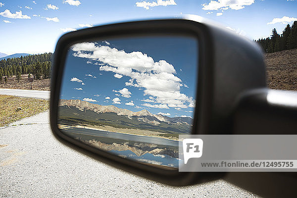 Idyllic lake is reflected in car's rear view mirror  Colorado