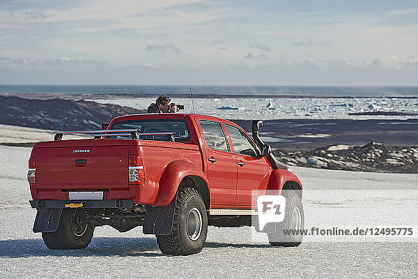 Man stopping and taking a picture from a customised Icelandic 4x4 pick up truck on the Breidamerkurjokull glacier  which is a part of the Vatnajokull glacier