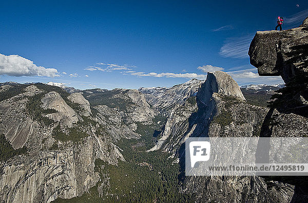 A backpacker stands on a rock clliff at Glacier Point overlooking Half Dome in Yosemite National Park.
