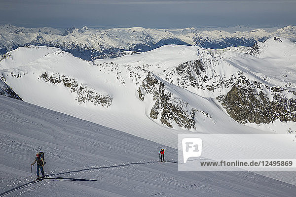 Skiers skin across a wide open expanse of snow during the Spearhead Traverse in the Coast Mountains of British Columbia  Canada.