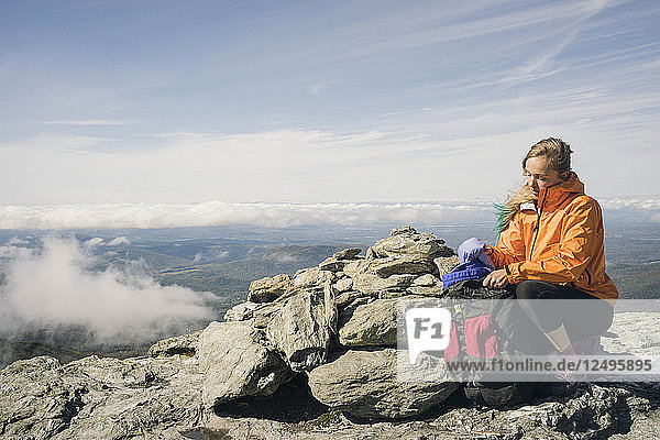 Female Hiker With Backpack Sitting On Rock In Mount Mansfield