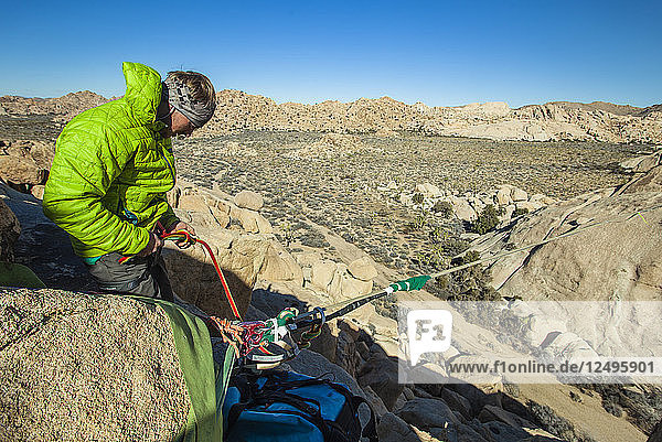 Man Tying Rope Into Highline In Joshua Tree National Park