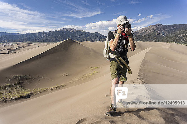 A male tourist in the sand dunes taking a picture