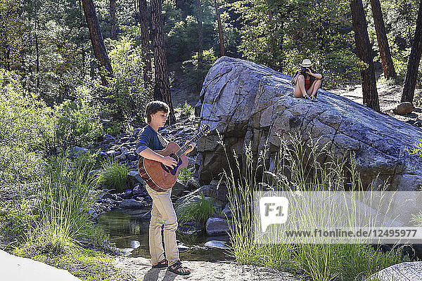 Young man plays guitar by a creek while a young woman looks on with camera.