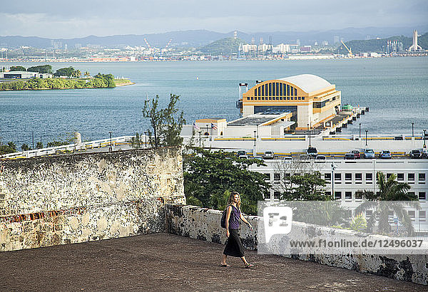 Woman Exploring A Fort Overlooking The Water Off The Coast Of San Juan  Puerto Rico