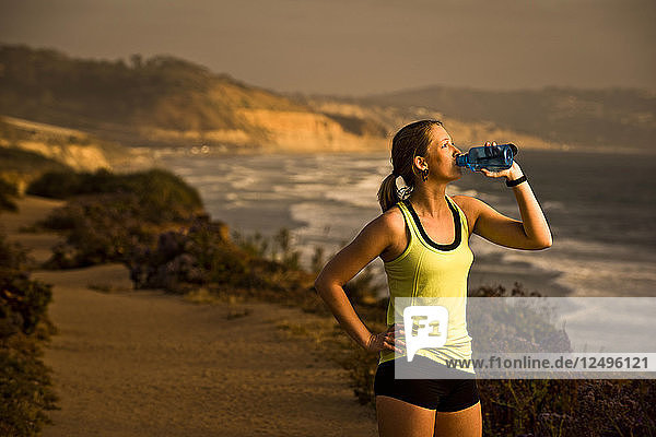 A girl drinks water while taking a break from her run on a trail overlooking the beach at sunset in San Diego  California.