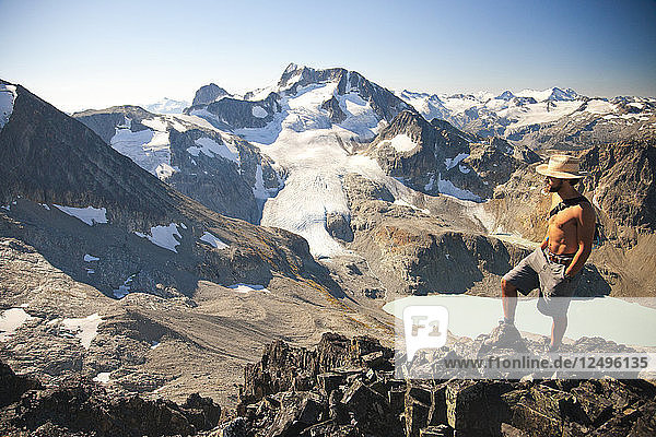 A hiker looks north east from the summit of Mount Cook with views of Wedge Mountain and Wedgemount Lake  a part of Garibaldi Provincial Park  are seen in the backdrop.