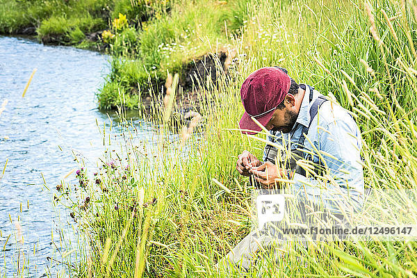 A Fly Fisherman Prepares His Gear While Sitting Next To The Yampa River  Colorado