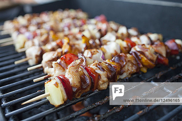 Chicken and vegetable skewers cooking on the BBQ.