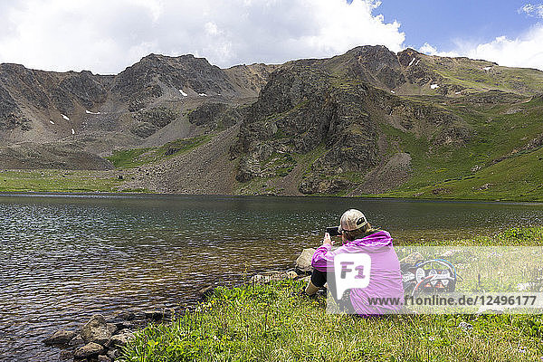 A young female sits along a high alpine lake and take a picture with her iphone