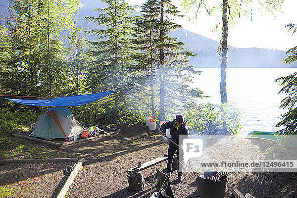 A woman tends to a fire while camping in Bowron Lake Provincial Park  British Columbia  Canada.
