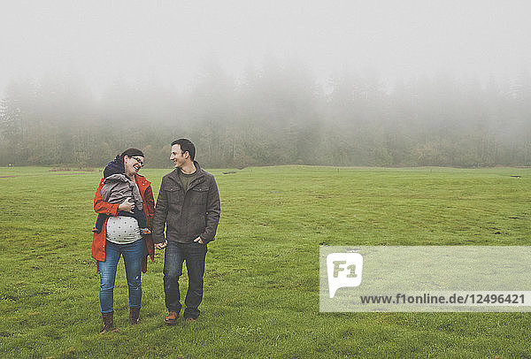 A pregnant mother holds her son while walking hand-in-hand with her husband at a local park.
