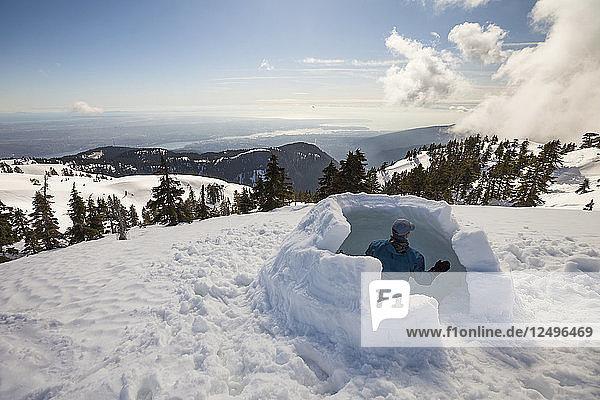 A Man Works To Build An Igloo On Seymour Mountain  Canada
