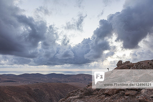 Photographer's silhouette in action in a dramatic landscape