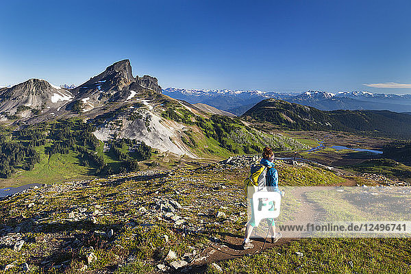A young woman backpacking on the Panorama Ridge Trail with Black Tusk Mountain in the background in Garibaldi Provincial Park  British Columbia  Canada.