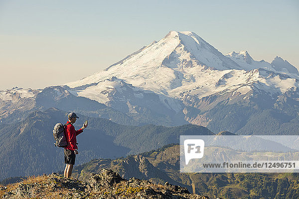 A Backpacker Checks His Phone While Hiking In North Cascades National Park