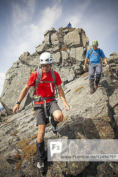 Three climbers descend from the summit of Trio Peak  British Columbia  Canada.