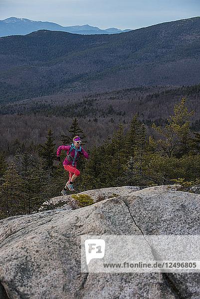 Trail runner Kristina Folcik running up the steep granite slab with Mount Washington in the distance.