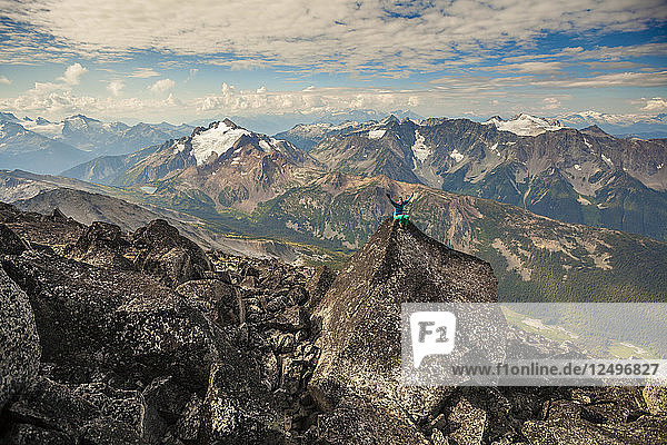 Long Exposure Of Female Climber Sitting On Top Of Mount Marriott