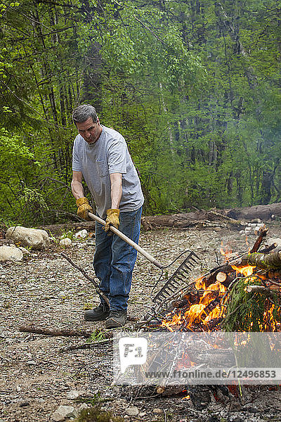 A middle aged man tends to a large fire while doing yardwork.