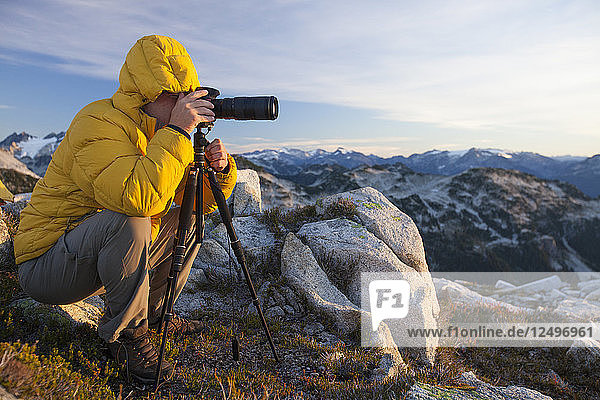 A photographer uses a tripod and a zoom lens to capture a landscape photo from the top of a rocky mountain ridge in British Columbia  Canada.