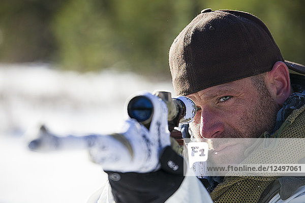 A hunter takes aim with his rifel  covered in white camouflage tape.