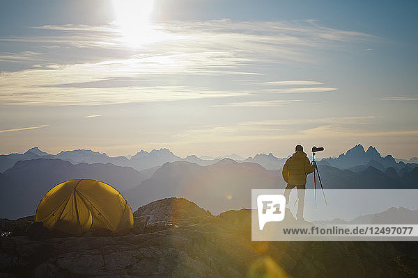A photographer enjoys the view from his campsite on a rocky mountain ridge in Pinecone Burke Provincial Park  British Columbia  Canada.