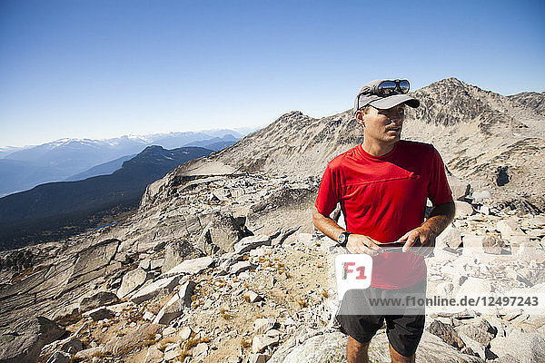 A hiker uses his smartphone to capture photos from the summit of Cassiope Peak near Pemberton  British Columbia  Canada.