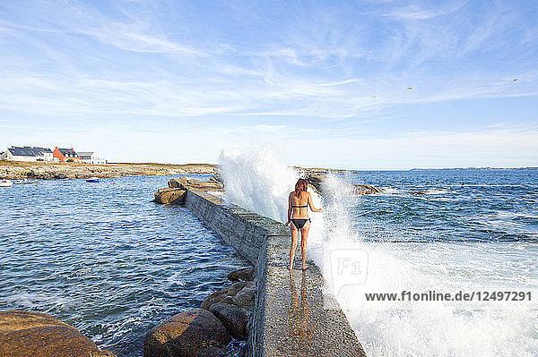 Woman Walking On Rock With Splashing Water In Ile De Croix  France