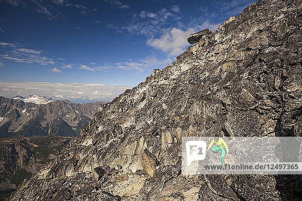 A Climber Scrambles Down A Rocky Ridge After Climbing Mount Marriott